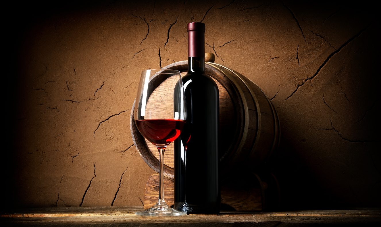 Old red wine in cellar near clay wall