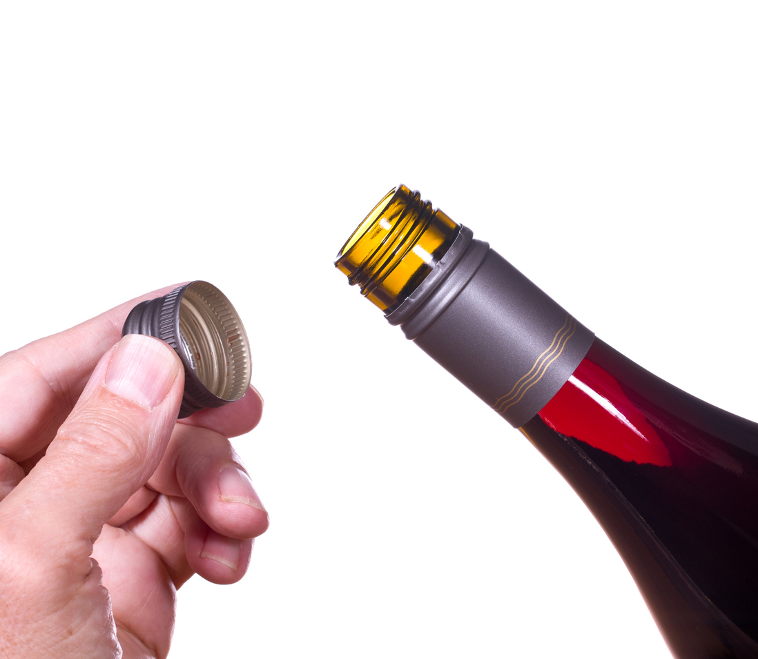 Red or rose wine in screw top wine bottle isolated against white with hand holding the cap by the neck of bottle
