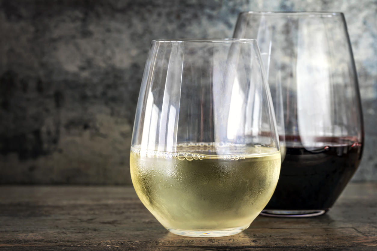 White and red wine in modern stemless glasses, with slate and timber background with copy space.